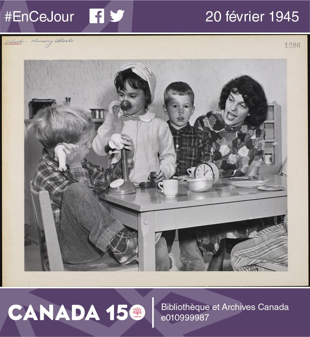 Photo d'enfants jouant au papa et à la maman autour d'une table en compagnie d'une adulte, date inconnue.